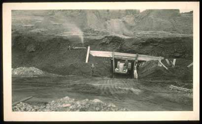 Early mining scene showing a method of loading a Truck wth a Dozer